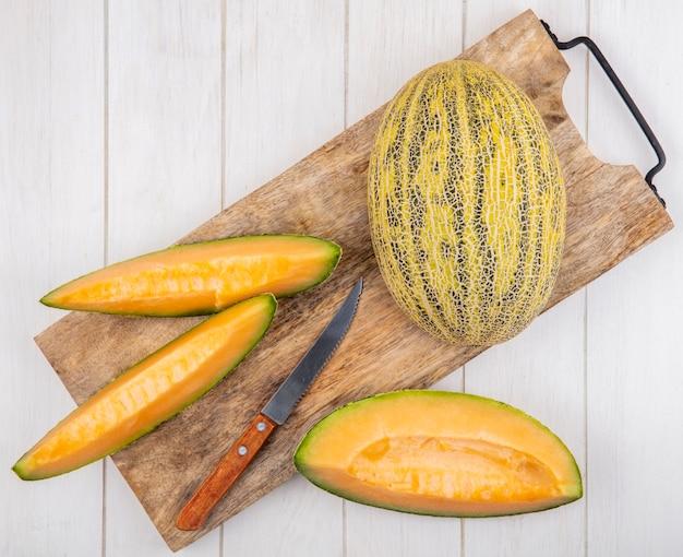 Draufsicht von frischen und köstlichen melonenscheiben auf hölzernem küchenbrett mit messer auf weißem holz