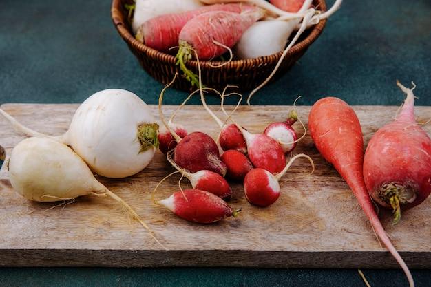 Draufsicht von frischen weißen und rosaroten wurzelgemüse-rote beete auf einem hölzernen küchenbrett mit radieschen auf einer grünen oberfläche