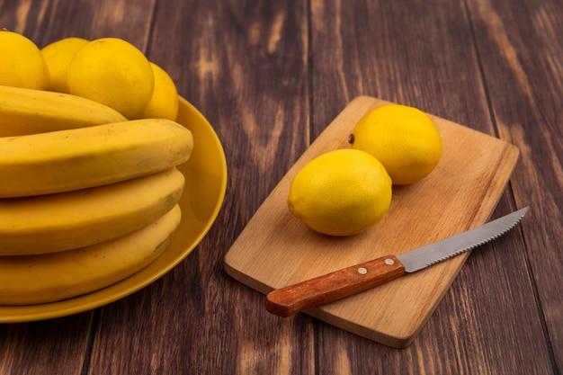 Draufsicht von frischen zitronen auf einem hölzernen küchenbrett mit messer mit zitronen auf einem gelben teller mit bananen auf einer hölzernen oberfläche
