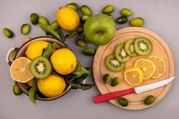 Draufsicht von frischen zitronen auf einer schüssel mit kiwi- und zitronenscheiben auf einem hölzernen küchenbrett mit messer mit kinkans und apfel lokalisiert auf einer weißen wand