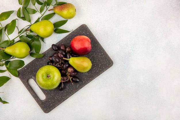 Draufsicht von früchten als birnenapfel-traubenpfirsich auf schneidebrett mit blättern auf weißem hintergrund mit kopienraum