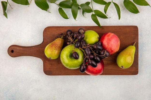 Draufsicht von früchten als birnenapfel-traubenpfirsich auf schneidebrett mit blättern auf weißem hintergrund