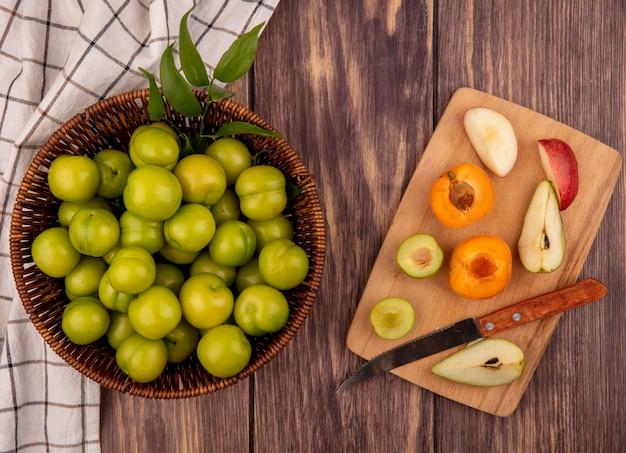 Draufsicht von früchten als grüne pflaumen im korb auf kariertem stoff und halb geschnittenem aprikosenbirnenpflaumenpfirsich mit messer auf schneidebrett auf hölzernem hintergrund