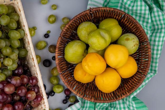 Draufsicht von früchten als grüne pluots und nectacots im korb auf kariertem stoff und korb von trauben mit traubenbeeren auf grauem hintergrund