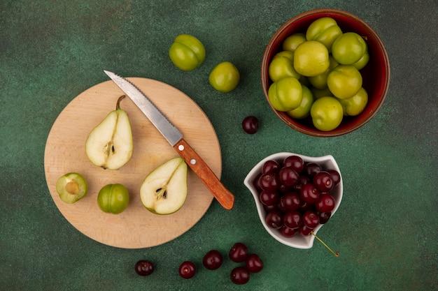 Draufsicht von früchten als halb geschnittene birne und pflaume mit messer auf schneidebrett und schalen von kirsche und pflaume auf grünem hintergrund