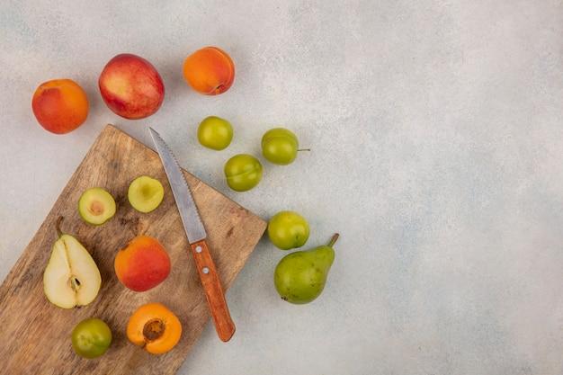 Draufsicht von früchten als halbgeschnittene birnenpflaumen-aprikose mit messer auf schneidebrett und muster von birnenpflaumen-aprikosenpfirsich auf weißem hintergrund mit kopienraum
