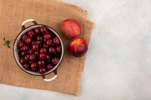 Draufsicht von früchten als kirschen in schüssel und pfirsichen auf sackleinen und weißem hintergrund mit kopienraum