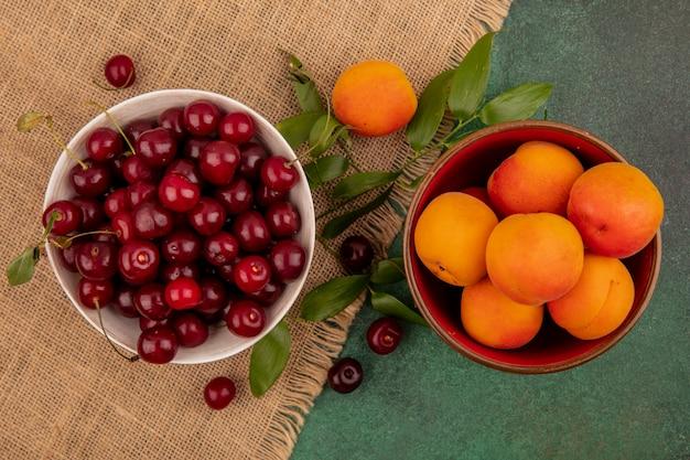 Draufsicht von früchten als kirschen und aprikosen in schalen mit blättern auf sackleinen auf grünem hintergrund