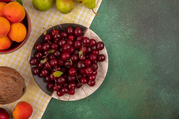 Draufsicht von früchten als kirschen und aprikosen in teller und schüssel mit birnen und kokosnuss auf kariertem stoff auf grünem hintergrund mit kopienraum