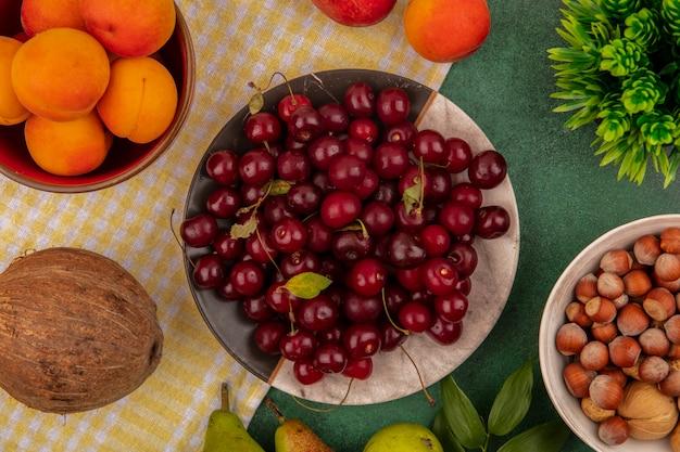 Draufsicht von früchten als kirschen und aprikosen in teller und schüssel mit birnen und kokosnuss auf kariertem stoff und schüssel nüssen auf grünem hintergrund