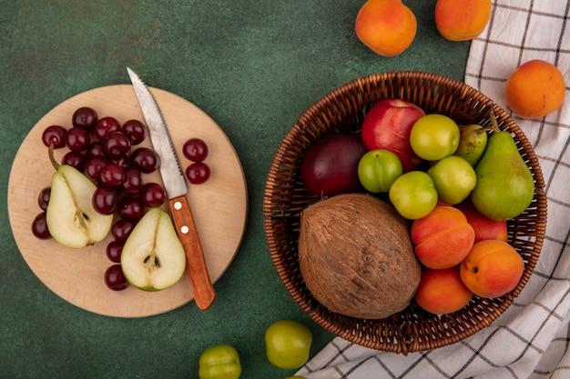 Draufsicht von früchten als kirschenbirnen-kokosnusspflaumen-aprikosenpfirsich mit messer im korb und auf schneidebrett auf kariertem stoff auf grünem hintergrund