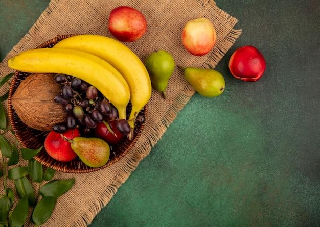 Draufsicht von früchten als kokosnussbananen-traubenbirnenpfirsich im korb und auf sackleinen auf grünem hintergrund