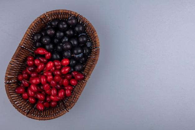 Draufsicht von früchten als kornelkirsche und schlehenbeeren im korb auf grauem hintergrund mit kopienraum