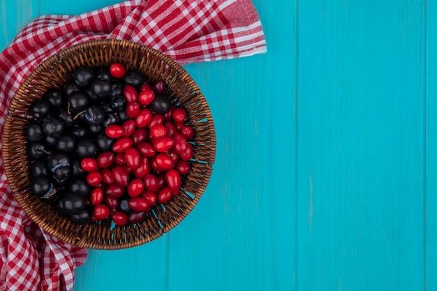 Draufsicht von früchten als kornelkirsche und schlehenbeeren im korb auf kariertem stoff auf blauem hintergrund mit kopienraum