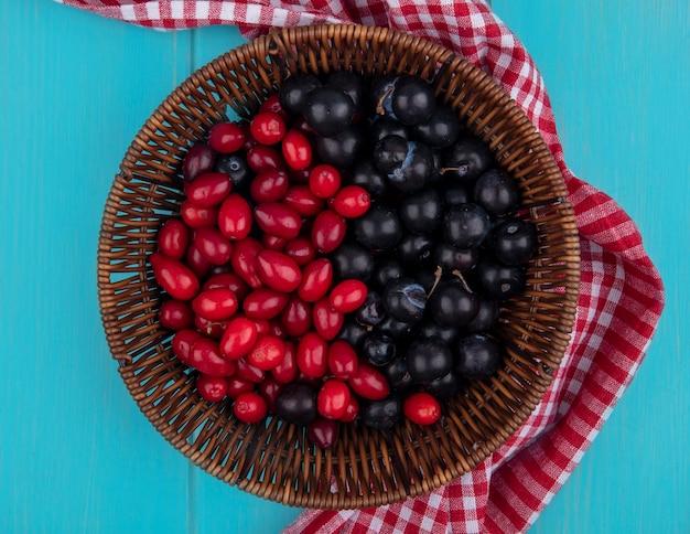 Draufsicht von früchten als kornelkirsche und schlehenbeeren im korb auf kariertem stoff auf blauem hintergrund