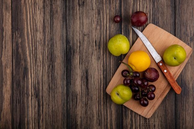 Draufsicht von früchten als nektakotgrün und geschmackskönig pluots traube mit messer auf schneidebrett auf hölzernem hintergrund mit kopienraum