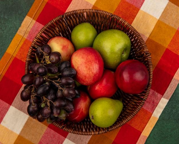 Draufsicht von früchten als pfirsichapfelbirnen-traube im korb auf kariertem stoff und auf grünem hintergrund