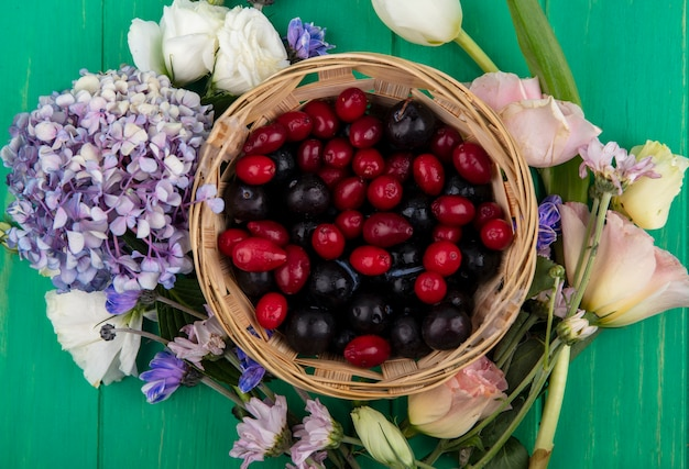 Draufsicht von früchten als schlehe und kornelkirschenbeeren im korb mit blumen herum auf grünem hintergrund