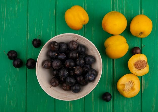 Draufsicht von früchten als schlehenbeeren in schüssel und aprikosen mit halbem schnitt auf grünem hintergrund