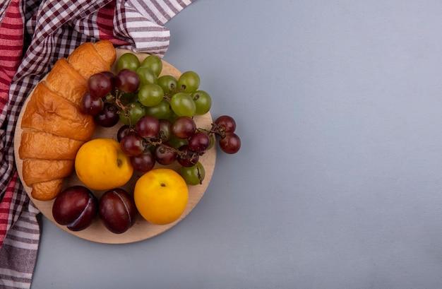 Draufsicht von früchten als traubennektakot und pluot mit croissant auf schneidebrett auf kariertem stoff auf grauem hintergrund mit kopienraum