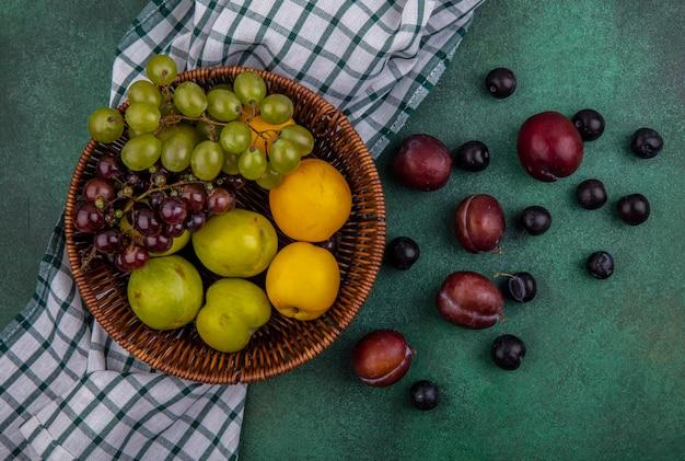 Draufsicht von früchten als traubenpluots und -nektakots im korb auf kariertem stoff und muster von pluots und traubenbeeren auf grünem hintergrund