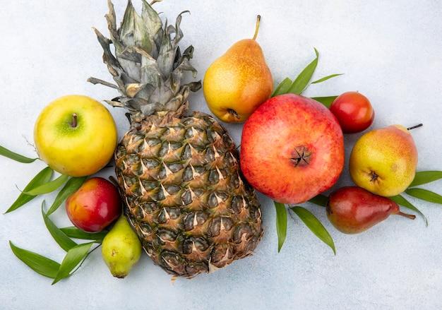 Draufsicht von früchten auf weißer oberfläche verziert mit blättern