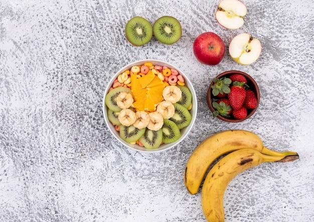 Draufsicht von früchten und maisringen in der schüssel mit kopienraum auf weißer oberfläche horizontal