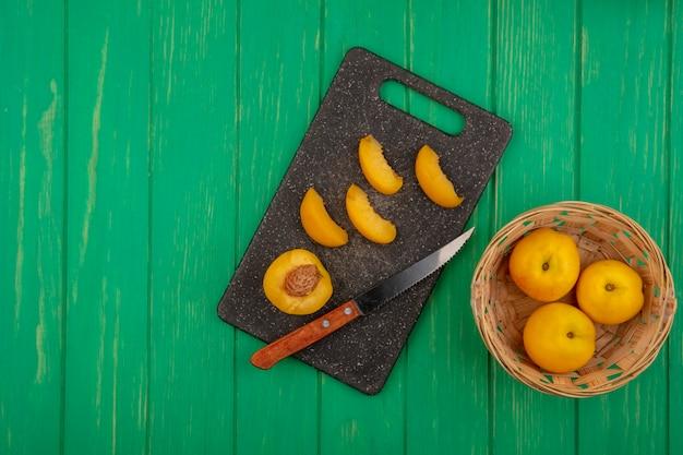 Draufsicht von ganzen aprikosen im korb mit der hälfte und in scheiben geschnittenen mit messer auf schneidebrett auf grünem hintergrund mit kopienraum