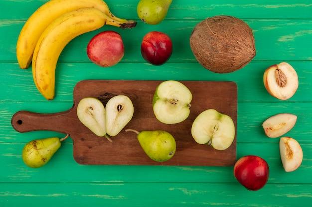 Draufsicht von ganzen und halben geschnittenen früchten als birnenapfel auf schneidebrett mit pfirsichbananenkokosnuss auf grünem hintergrund