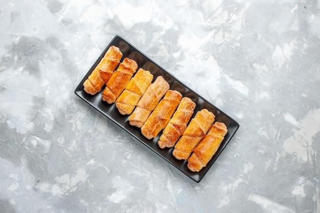 Draufsicht von gebackenen köstlichen armreifen innerhalb des schwarzen schimmelpilzes auf grauem gebäck backen kekskuchen süß