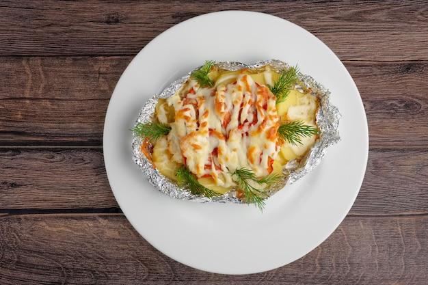Draufsicht von gebraten im folienseefisch und -kartoffel mit paprika und käse auf holztisch