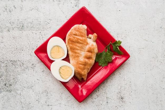 Draufsicht von gebratenen hühnerflügeln mit gekochtem ei in der roten platte über konkretem boden