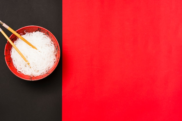 Draufsicht von gedämpften weißen suppennudeln in der schüssel mit essstäbchen über doppelhintergrund