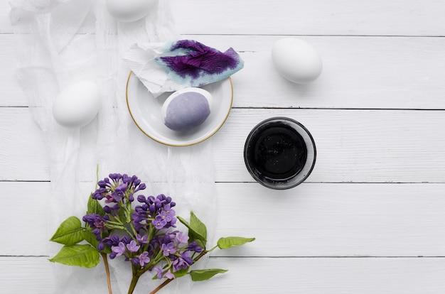 Draufsicht von gefärbten eiern für ostern mit lila blumen