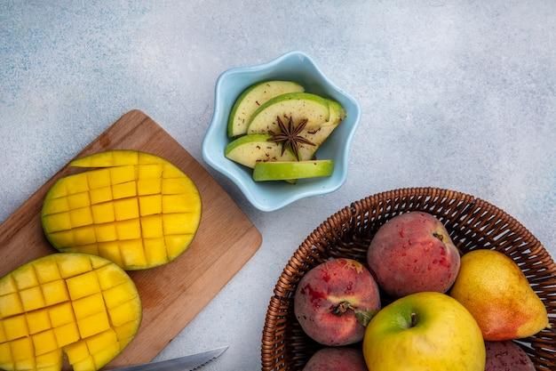 Draufsicht von gehackten grünen äpfeln in einer weißen schüssel mit geschnittener mango auf hölzernem küchenbrett und pfirsichen auf eimer auf weiß