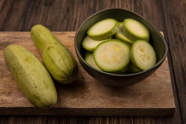 Draufsicht von gehackten zucchini auf einer schüssel mit ganzen zucchini lokalisiert auf einem hölzernen küchenbrett auf einer holzwand