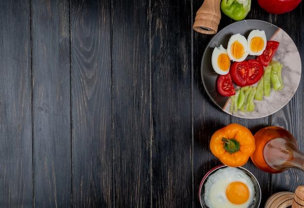 Draufsicht von gekochten eiern auf einem teller mit tomatenscheiben mit apfelessig auf einem hölzernen hintergrund mit kopienraum
