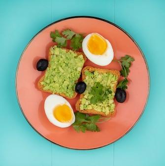 Draufsicht von gekochten eiern mit geröstetem brot mit avocadopulpen mit oliven auf orangeem teller auf blau