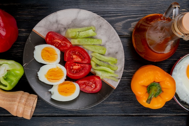 Draufsicht von gekochten halbierten eiern auf einem teller mit paprika mit apfelessig auf einem hölzernen hintergrund