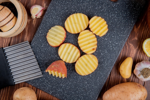 Draufsicht von gekräuselten kartoffelscheiben auf schneidebrett mit ganzen zitronenknoblauch auf holz herum
