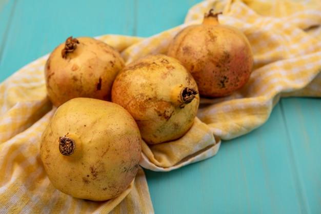 Draufsicht von gelben granatäpfeln lokalisiert auf einem gelben karierten tuch auf einer blauen holzoberfläche