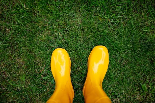 Draufsicht von gelben gummistiefeln auf dem gras