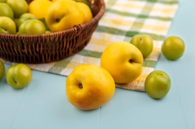 Draufsicht von gelben pfirsichen mit grünen kirschpflaumen auf einer karierten tischdecke auf einem blauen hintergrund