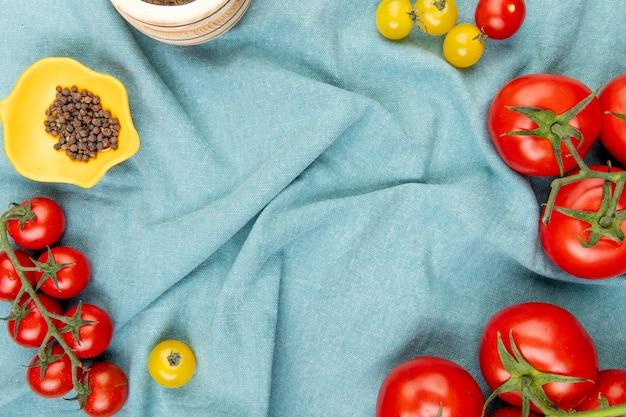 Draufsicht von gelben und roten tomaten mit schwarzen pfeffersamen auf blauem stofftisch