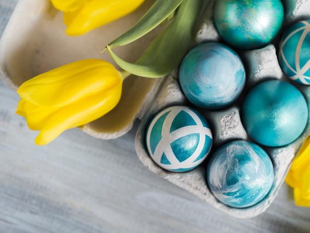 Draufsicht von gemalten ostereiern im karton mit tulpen