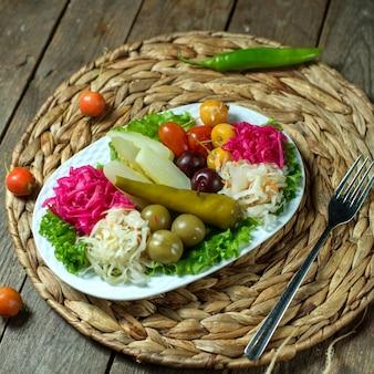 Draufsicht von gemischten gurkenkohlolivengurken und -pfeffer auf einer platte