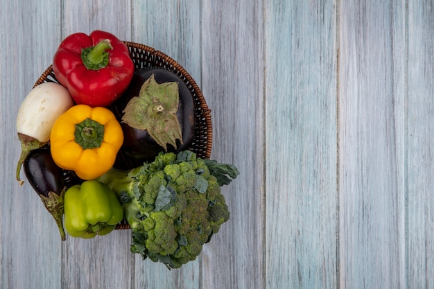 Draufsicht von gemüse als brokkoli-pfeffer und aubergine im korb auf hölzernem hintergrund mit kopienraum