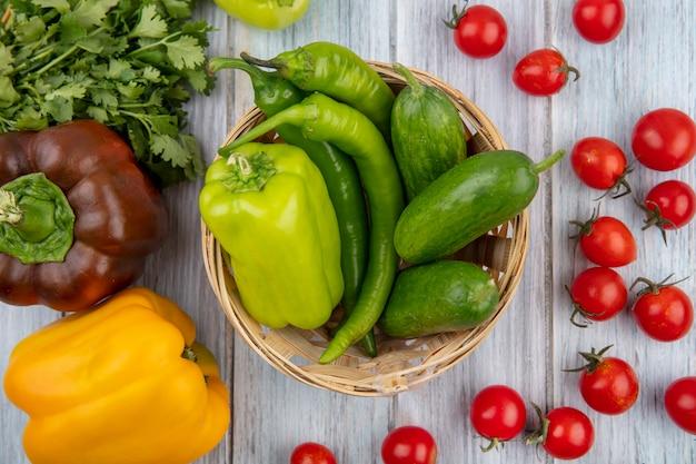 Draufsicht von gemüse als pfeffer und gurke im korb mit koriander und tomaten herum auf holzoberfläche