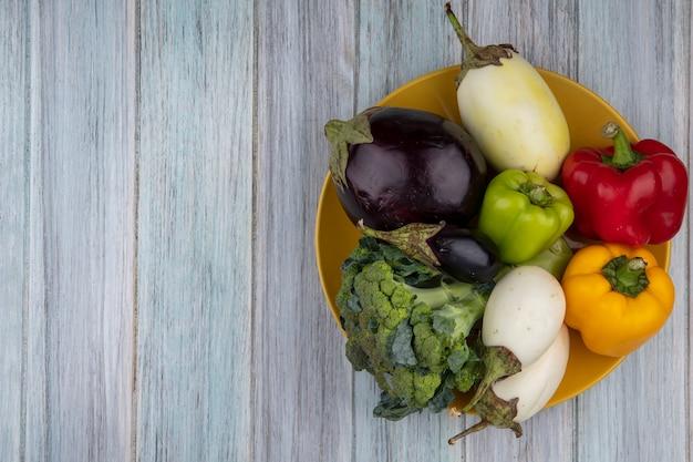 Draufsicht von gemüse als pfefferbrokkoli und aubergine in platte auf hölzernem hintergrund mit kopienraum