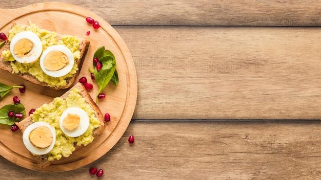 Draufsicht von geröstetem brot mit gekochtem ei auf schneidebrett